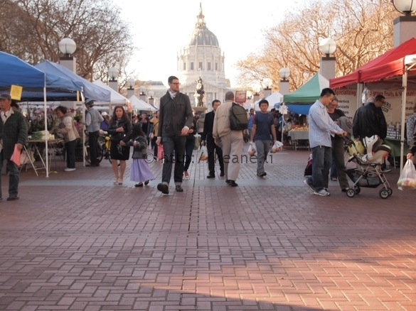 Tall man walking through the Heart of the City Farmers' Market in Civic Center SF (photo)