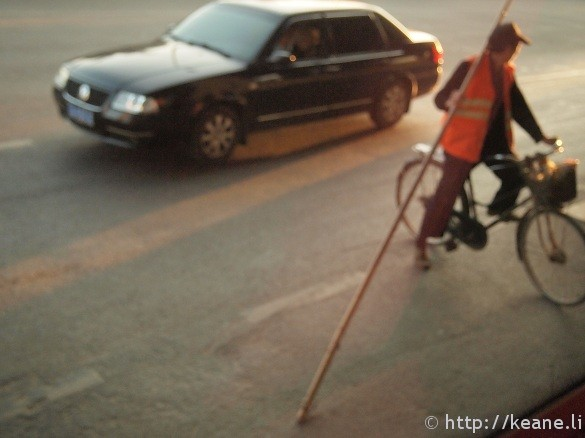 Blurry photo of a man on bike with a long stick in Kunming