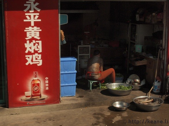 Woman cleans vegetables in a city in Yunnan