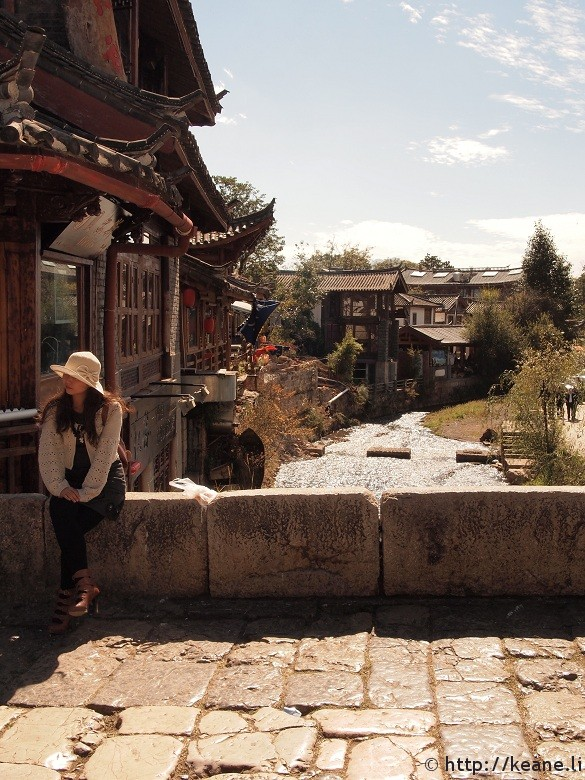 Woman sitting along Qinglong Bridge in Shu He Ancient City in Lijiang