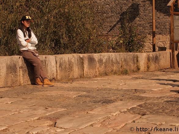 Pretty Chinese woman in NYC cap along Qinglong Bridge in Shu He Ancient City