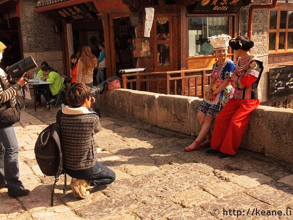 Couple in traditional Chinese clothing pose on Qinglong Bridge in Lijiang