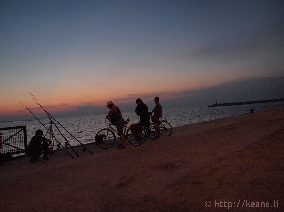 Fishermen along the Rimini pier at sunset